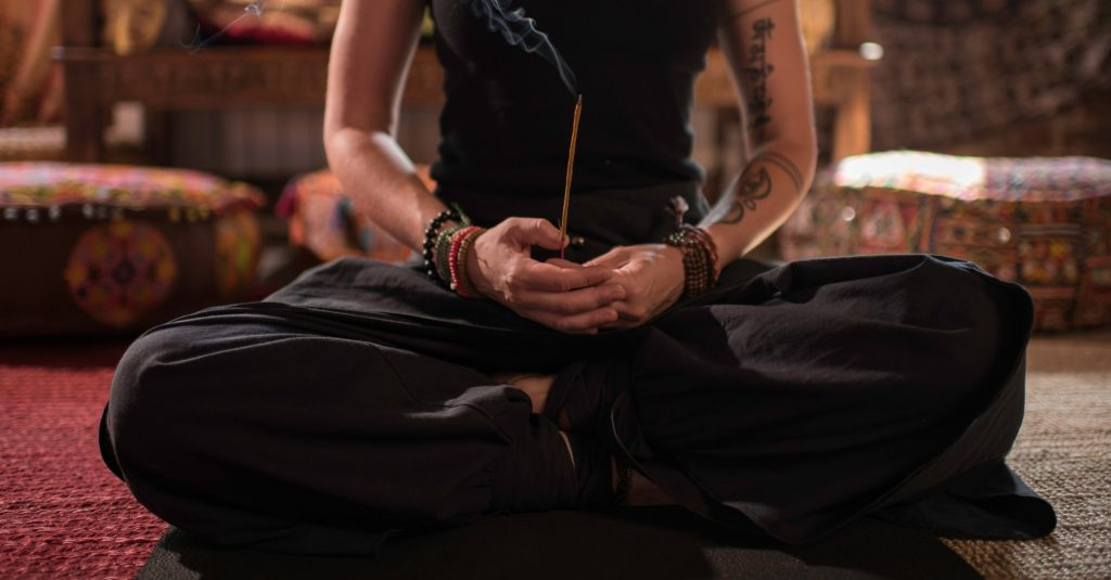Close up of woman hands holding a scented stick and doing yoga